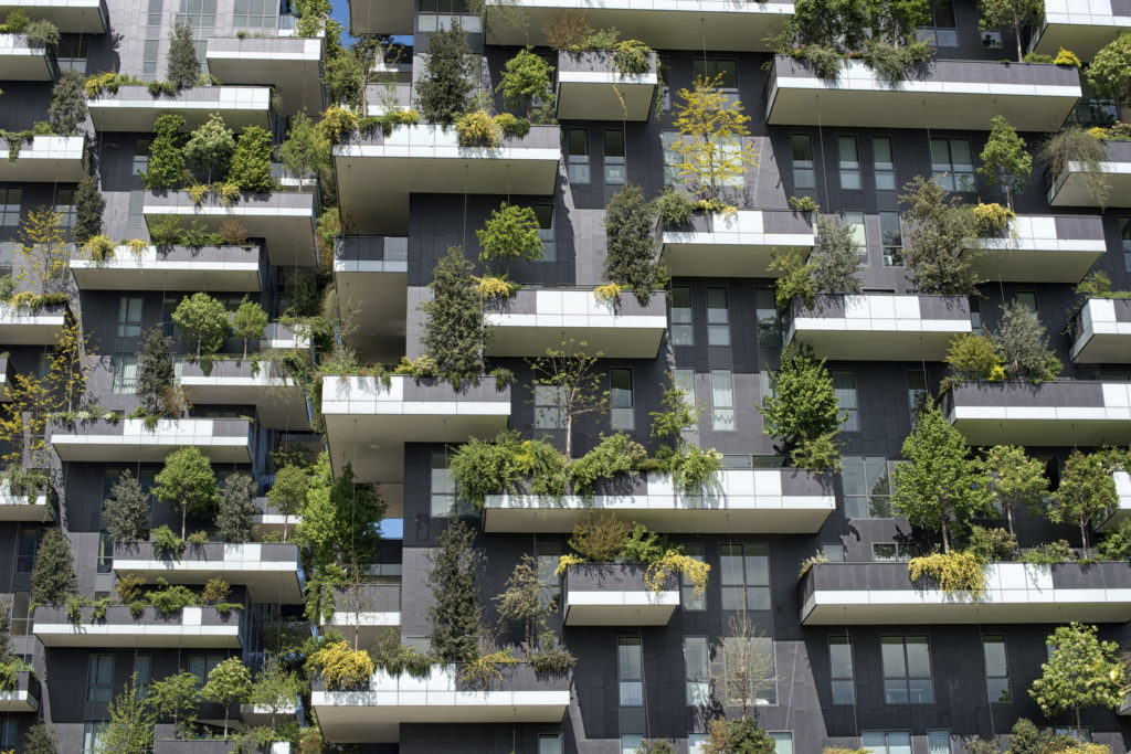 Tight detail view on trees and shrubs on vertical forest apartment building in downtown Milan, Italy