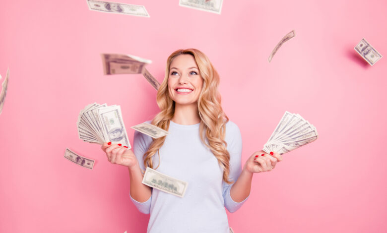 Młoda kobieta stoi na różowym tle i trzyma banknoty do oszczędzania