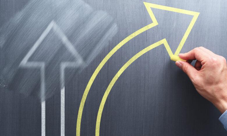 Ręka rysuje strzałki kredą na tablicy symbolizujące kierunek zmian w firmie